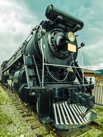 exhibit locomotive stands on rails. Big black locomotive.
