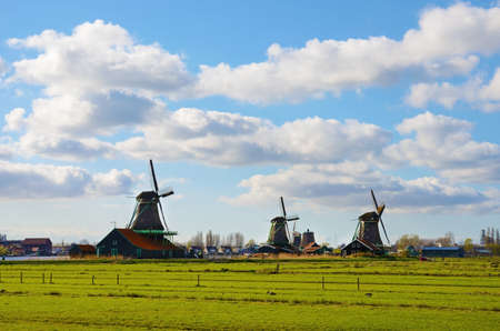 The picturesque landscape with aerial mill on the channel in Zaanse Schans, Holland on a background cloudy sky