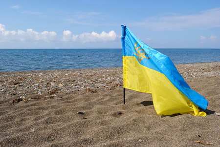 annexation: Flag of Ukraine against the backdrop of the sea on the coast of the Crimea (the annexation of the Crimea, War in Ukraine - concept)