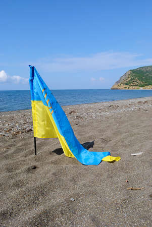 Flag of Ukraine against the backdrop of the sea on the coast of the Crimea (the annexation of the Crimea, War in Ukraine - concept)