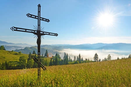 pilgrimage: Cross-crucifixion in the field on a sunny day with fog in the mountains (pilgrimage, harmony, inspiration, peace - concept)