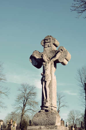 stone tombstone: Old stone statue of Jesus crucified on the cross on the tombstone in the cemetery in Ukraine in vintage style Stock Photo