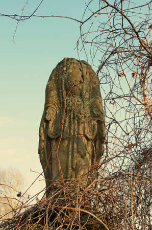 headstone: The old stone statue with the missing head on the headstone in the cemetery in Ukraine in vintage style
