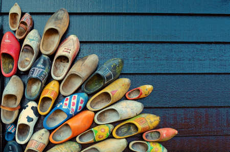 klompen: traditional wooden shoes in all sizes and colors hanging on a wall(welcoming background for postcards, greeting from the Netherlands) Stock Photo