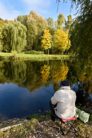 hobbies: A man fishing on the pond in autumn (hobbies, loneliness, pension - concept) Stock Photo
