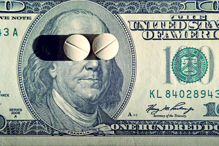 aging concept: Tablets on dollar bills (treatment, addiction, aging - concept). Vintage effect. Stock Photo