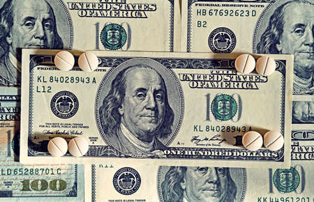 aging concept: Tablets on dollar bills treatment, addiction, aging - concept. Vintage effect.
