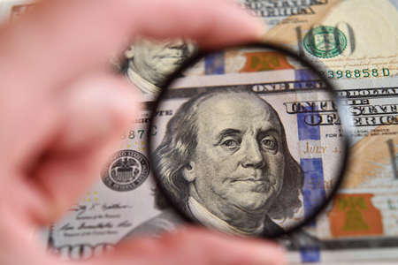 Dollar banknote through magnifying lens (corruption, lobbying, inflation, financial secrecy - concept).
