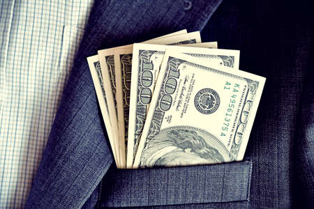 Dollars in the pocket of jacket (corruption, lobbying, bribery - concept). Stock Photo