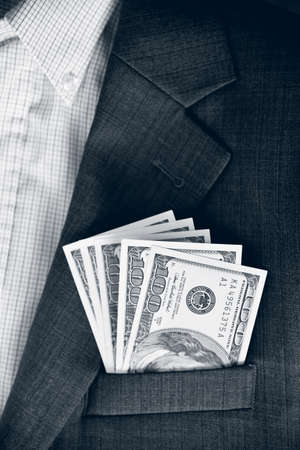 lobbying: Dollars in the pocket of jacket (corruption, lobbying, bribery - concept). Vintage effect.