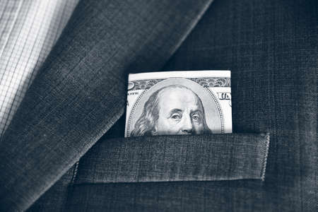 lobbying: Dollars in the pocket of his jacket (corruption, lobbying, bribery - concept). Vintage effect. Stock Photo