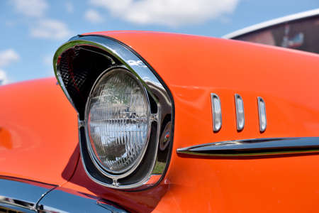 collectible: Headlight retro car on background of cloudy sky. Vintage.