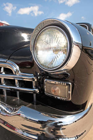 collectibles: Headlight retro car on background of cloudy sky. Vintage. (Luxury, wealth, major - concept)