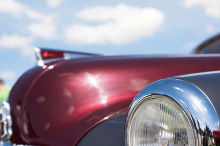 collectible: Headlight retro car close-up on a background of the cloudy sky.