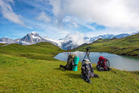 trekking pole: Backpacks, trekking pole and camera on a tripod in the mountains in the Swiss Alps, Europe (still life coach, company, friendship, background - concept)
