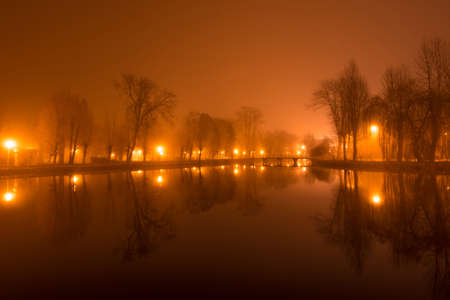 lake sunset: Mystical landscape with trees near the pond in misty autumn evening