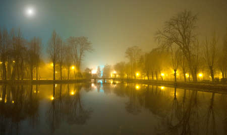 lake sunset: Mystical landscape with trees near the pond in misty autumn evening in the moonlight Stock Photo