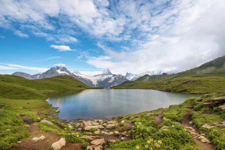Paysage fantastique avec lac dans les Alpes suisses, Europe. Wetterhorn, Schreckhorn, Finsteraarhorn et Bachsee. (Paysage, détente, tourisme, anti-stress - concept). Banque d'images - 74051638