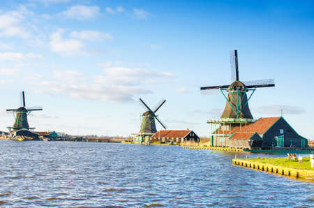 zaan: Scenic picture of the water and windmills in Zaanse Schans, Holland, Europe against the backdrop of a cloudy sky. Stock Photo