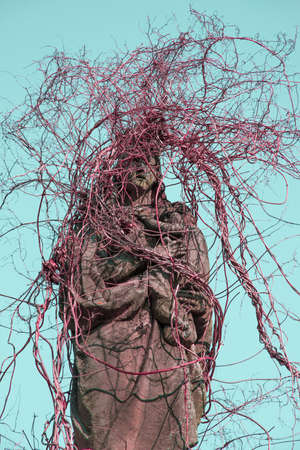 Creepy mystical  old  figure of Mary with little Jesus. Sculpture overgrown with ivy like braids. Vintage style. Stock Photo