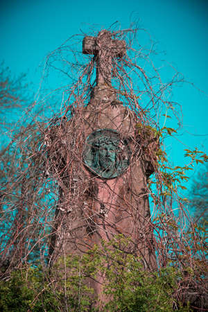 Mystical creepy tombstone depicting the face of Jesus Christ, overgrown with ivy. Vintage style. Stock Photo