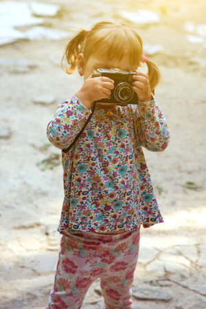 A little girl is photographing a retro camera
