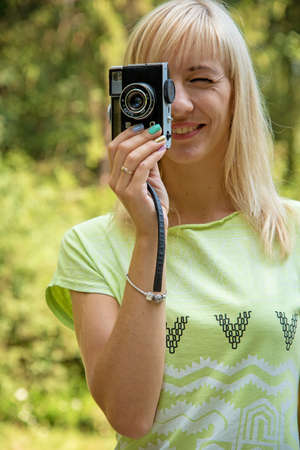 beginner: A beautiful young girl with a camera in the park on a sunny day