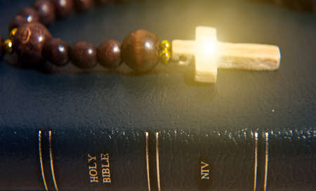 The wooden rosary  on the Bible with a cross that radiates light