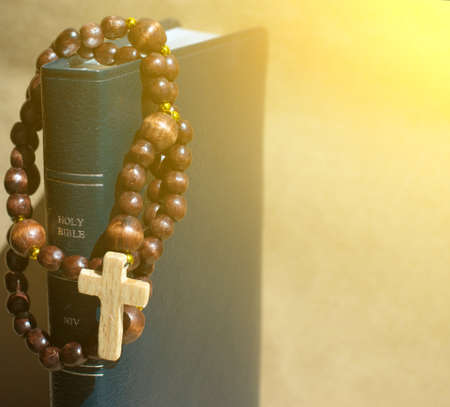 jehovah: spiritual background with Wooden rosary on the Bible in the aureole of the divine of Divine Rays and place for inscription