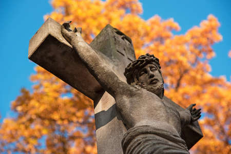 Crucifixion of Jesus Christ on a stone cross on the background of an orange autumn tree as a symbol of suffering and salvation of mankind after death in the kingdom of eternity. Stock Photo