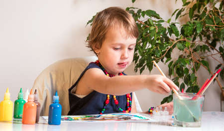A beautiful little girl concentrates on drawing a picture with colored paints