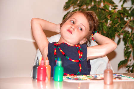 A beautiful, pretty little girl thinks over which colors to add to her life for a happy, carefree childhood.