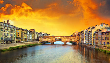 Beautiful city view with the famous medieval stone bridge Ponte Vecchio over the Arno river in Florence, Italy at sunset. Place of pilgrimage for tourists. Stockfoto