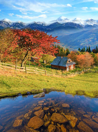 Beautiful landscape with stones in the lake and hut in the autumn mountains against the background of snow-capped peaks. Stockfoto