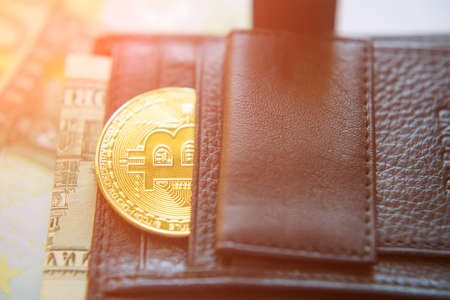 bitcoins and a dollar bill in a leather black wallet (Investment, exchange rate, rise, decline, luxury, success, stock exchange - concept)