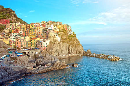 Charming beautiful landscape with bright colored houses on the rock on the seafront of Manarola in Cinque Terre, Liguria, Italy, Europe in sunlight