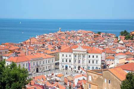 Beautiful scenery with tiled houses and roofs in the central square against the background of the blue sea in Porets, the tourist center of Croatia