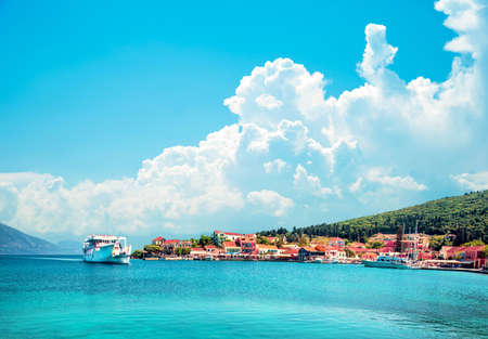 Beautiful scenic landscape with bay and ferry on the background of magical clouds in Nydri, Lefkada, Greece. Stunning amazing charming places. prominent tourist towns. 스톡 콘텐츠