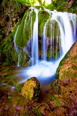 charming, magnificent landscape with a waterfall in the forest between the rocks