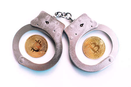 Bitcoins and handcuffs as an abstract symbol of crime that can hide cryptography