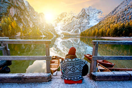 Amazing fascinating magical autumn winter landscape with a girl playing guitar over a lake on Fanes-Sennes-Braies natural park in the Dolomites in South Tyrol, Alps, Italy, Europe. (meditation, relaxation, stress relief, harmony - concept)