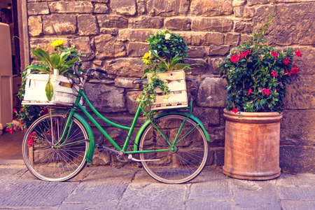 Beautiful city landscape with a green bike near the old wall with flowers in drawers in Florence, Italy, Europe.