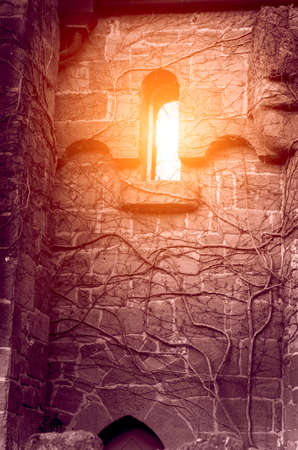 Mystical abstract image with light in the window of an ancient castle with shaded walls (Halloween, October 31 - concept)