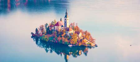 Magical autumn landscape with the island on Lake Bled (Blejsko jezero). Julian Alps, Slovenia, Europe. Attractions. Tourist places of pilgrimage. (Meditation, travel, inner peace, harmony, honeymoon - concept)