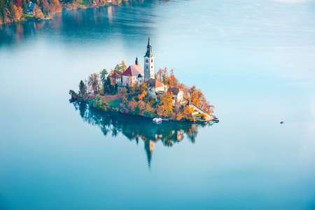 Magical autumn landscape with boat near island on Lake Bled (Blejsko jezero). Julian Alps, Slovenia, Europe. Attractions. Tourist places of pilgrimage. (Meditation, travel, inner peace, harmony, honeymoon - concept)
