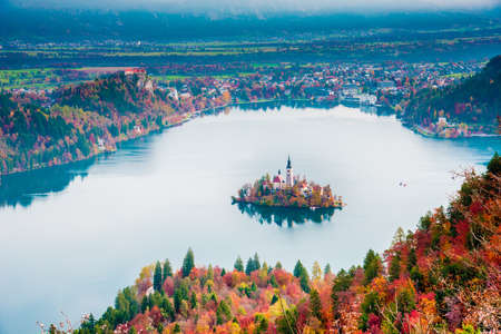 Incredibly beautiful landscape with church on the island in the middle of autumn forest in Bled, Slovenia. Attractions. (romance, harmony, meditation - concept)