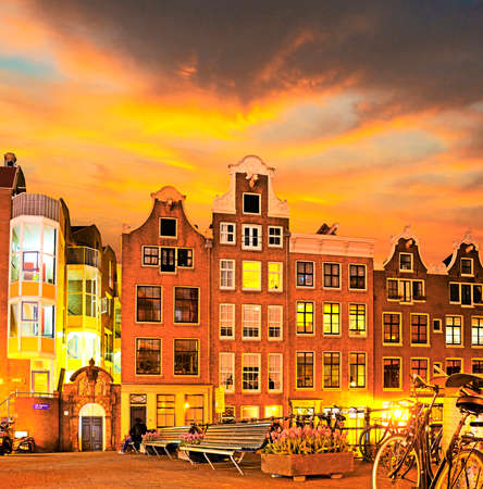 Outdoor landscape with old houses and bicycles and tulips at sunset in Amsterdam, The Netherlands. Light blur effect