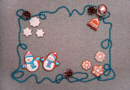 charming atmospheric christmas background with cones and celebratory biscuits in the form of snowflakes, bells and snowmen as a symbol of the new year 2019 (greeting card, greetings - concept)