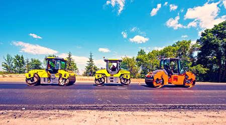 道路に新しいアスファルトを転がすローラーと工業景観。修理、複雑な輸送の動き。 写真素材