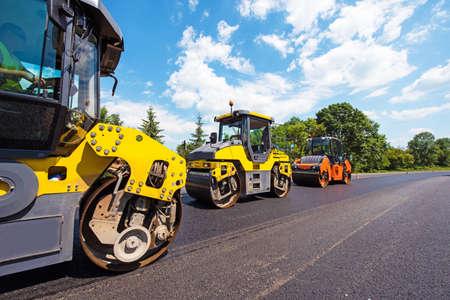 道路に新しいアスファルトを転がすローラーと工業景観。修理、複雑な輸送の動き。